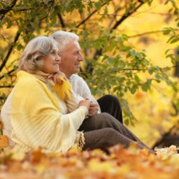 older couple sitting in the park in fall